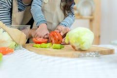 关闭手母亲和烹调和切开在厨房的孩子女孩菜 图库摄影