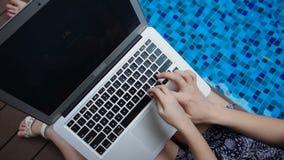 关闭打字在膝上型计算机键盘在蓝色游泳池附近 股票录像