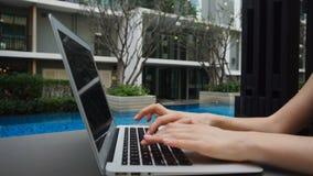 关闭打字在膝上型计算机键盘的手在慢动作的游泳池附近 影视素材