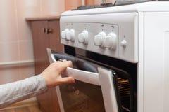 关闭打开烤箱门的妇女手控制在煤气炉的烘烤 免版税库存照片