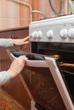 关闭打开烤箱门的妇女手控制在煤气炉的烘烤 库存照片