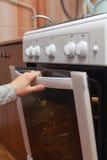 关闭打开烤箱门的妇女手控制在煤气炉的烘烤 图库摄影