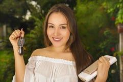 关闭把握她的关键在一只手上的一个微笑的美丽的少妇和片剂和钱包在她的其他手上  免版税库存照片