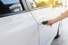 关闭把握汽车关键的手母司机使用门户开放主义的汽车 图库摄影