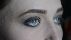 关闭投入在式样` s眼睛和眉头的构成的化妆师有一个红色成熟蕃茄的cosmeticmacro图象的在一绿色vin的 影视素材