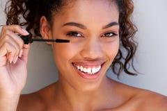 关闭投入在染睫毛油的美丽的年轻黑人妇女 库存图片