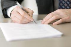 关闭投入署名的男性手 免版税库存图片
