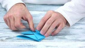 关闭折叠origami形象的男性手 股票视频