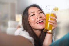 关闭拍与手机的年轻美丽和愉快的亚裔中国妇女面孔画象selfie照片喝橙色ju 免版税库存图片