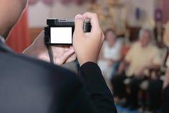 关闭拍与照相机的人的手一张照片在婚礼背景中 免版税库存图片