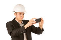 关闭拍照片的年轻工程师使用电话 免版税库存图片