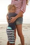 关闭拥抱儿子的母亲夏天海滩假期 库存图片