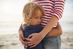 关闭拥抱儿子的母亲夏天海滩假期 免版税库存照片