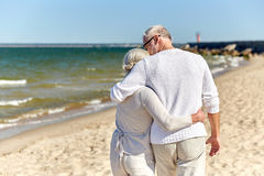关闭拥抱在海滩的愉快的资深夫妇 免版税库存照片