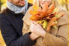 关闭拥抱在秋天公园的微笑的夫妇 免版税库存图片