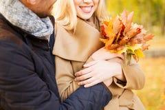关闭拥抱在秋天公园的微笑的夫妇 免版税库存照片