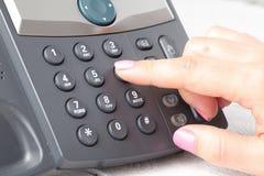 关闭拨号的手指打一个电话在办公室 免版税库存图片