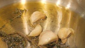 关闭拨蒜油煎在油用香料和草本在煎锅的油 免版税图库摄影