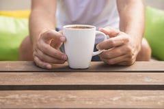 关闭拿着一个咖啡杯有外面绿色背景的人的手 免版税库存图片
