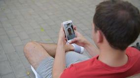 关闭拿着一个巧妙的电话的一只男性手在与他的朋友的录影电话期间 股票视频