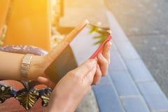 关闭拿着一个手机的商人的手户外 免版税库存照片