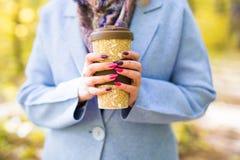 关闭拿着一个杯子在秋天街道上的外带的咖啡杯的妇女 免版税库存图片