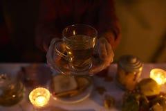 关闭拿着一个杯子用在黑暗的backg的茶的男性手 免版税库存照片