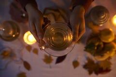 关闭拿着一个杯子用在黑暗的backg的茶的男性手 库存图片