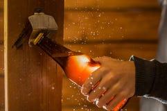 关闭拿着一个瓶工艺啤酒的一个人使用一个开启者,在木背景 库存照片