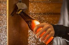 关闭拿着一个瓶工艺啤酒的一个人使用一个开启者,在木背景 免版税库存照片