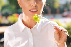 关闭拿着一把叉子用沙拉的妇女 免版税库存图片
