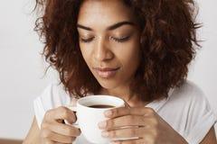 关闭拿着与闭合的眼睛的非洲女孩画象杯子嗅到的咖啡 醒早晨是坚韧的为 免版税库存图片