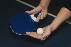 关闭拿着乒乓球火箭和球的一个人手 库存照片