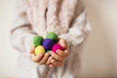 关闭拿着五颜六色的毛毡球的儿童手 孩子,孩子棕榈 一个小女孩在极少数保留色的羊毛球 免版税库存图片