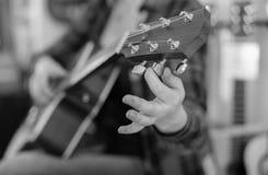 关闭拿着吉他钉的手指 免版税库存照片