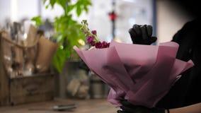关闭拿着在一个欢乐封皮的妇女卖花人美丽的花束 股票录像