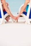 关闭拿着在椅子的资深夫妇手海滩 库存图片