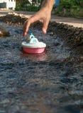 关闭拿着在河小河的男性手塑料玩具小船 免版税库存图片