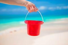 关闭拿着在热带海滩的手一个小红色桶 免版税图库摄影