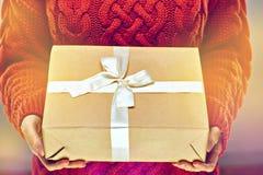关闭拿着在被编织的红色毛线衣背景的妇女手照片纸礼物盒 免版税库存照片