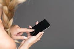关闭拿着她巧妙的电话的妇女 免版税库存照片
