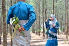 关闭拿着婚姻的花花束的新郎看她的新娘 免版税库存照片