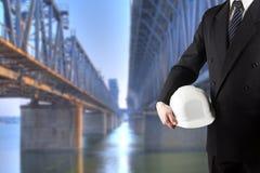 关闭拿着工作者安全的工程师手白色安全帽站立在有cra的被弄脏的建造场所前面 图库摄影