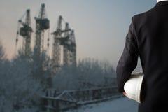 关闭拿着工作者安全的工程师手白色安全帽站立在有cra的被弄脏的建造场所前面 免版税库存图片