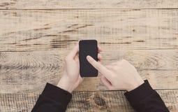 关闭拿着智能手机和指向手指的男性手注标和发短信在屏幕上在桌木板条 行家样式 T 免版税库存图片