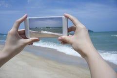 关闭拿着智能手机,机动性,在被弄脏的美丽的蓝色海的巧妙的电话的妇女的手拍海的照片 库存图片