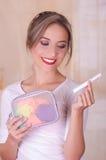 关闭拿着月经棉花棉塞的一名年轻美丽的微笑的妇女在她的手和一个五颜六色的钱包旅馆上 库存图片