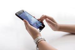 关闭拿着有企业图的女性手智能手机 图库摄影