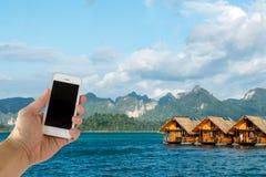 关闭拿着有黑屏的亚洲男性手巧妙的手机在海、蓝天和豪华浮动旅馆,当旅行T时 免版税图库摄影
