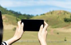 关闭拿着有黑屏的女性手巧妙的手机有山和Ranong,泰国清楚的天空的在背景中 免版税库存照片